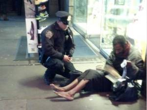 A policeman stops to give a barefoot street person boots