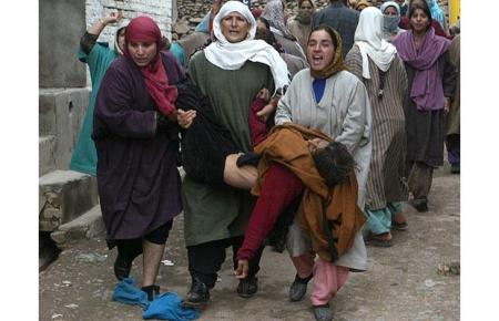 An unconscious Kashmiri woman is carried away during election violence