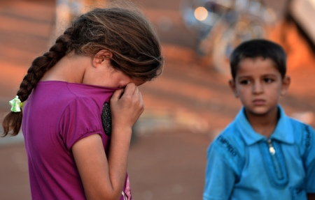 A young Syrian girl wiped her tears after not being allowed entry to Turkey for shelter last month.