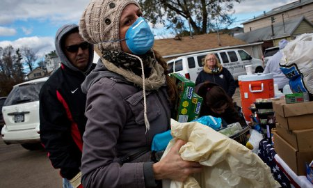 In the aftermath of Hurricane Sandy, a woman carries donated supplies to victims