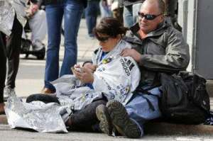 A survivor of the Boston Marathon bombing is comforted