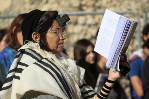 A woman attempts to pray at the Western Wall in December 2012 wearing a prayer shawl and tallitot.
